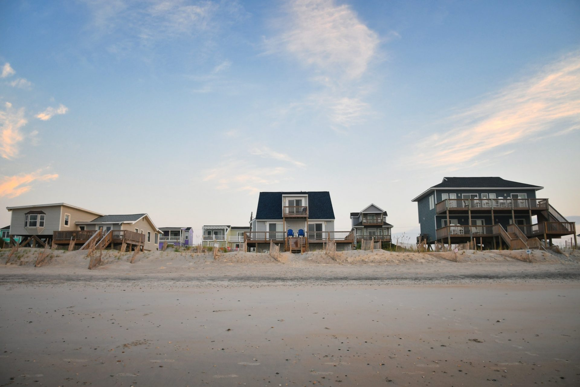 Row of various sized beach cottage vacation homes to rent or buy on the ocean