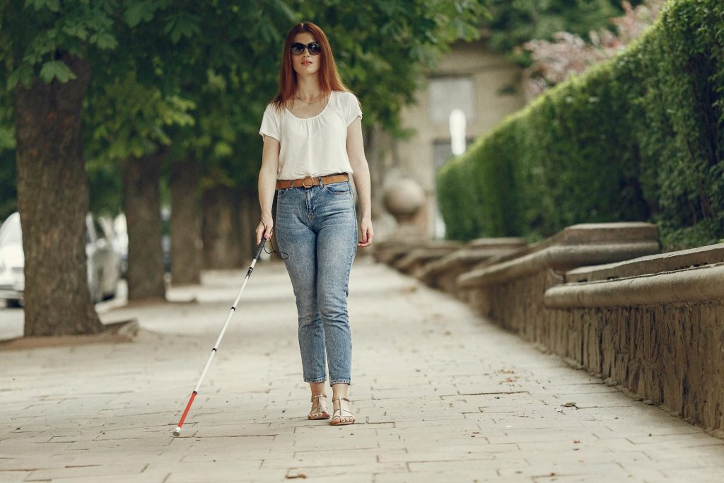 Young blind person with long cane walking in a city