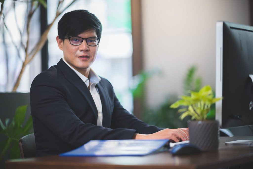 portrait of businessman in co-working space, handsome CEO smiling in suit